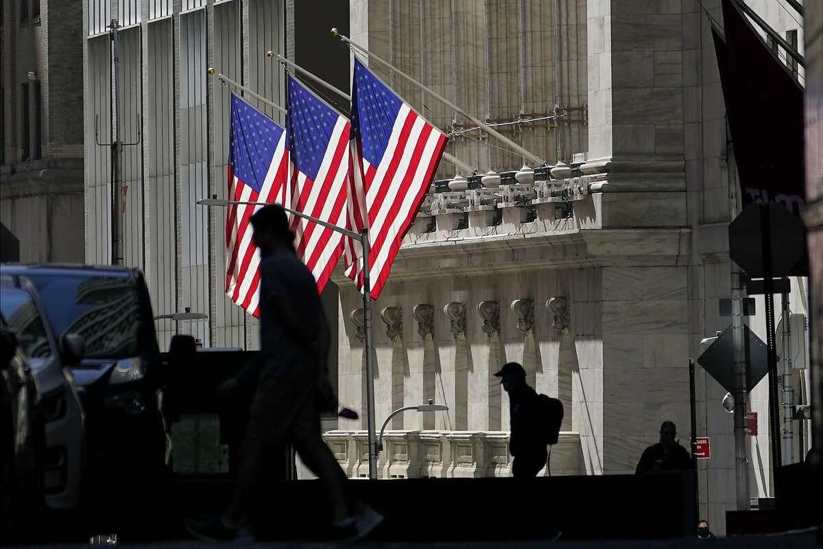 FILE - In this Oct. 14, 2020 file photo, pedestrians pass the New York Stock Exchange.