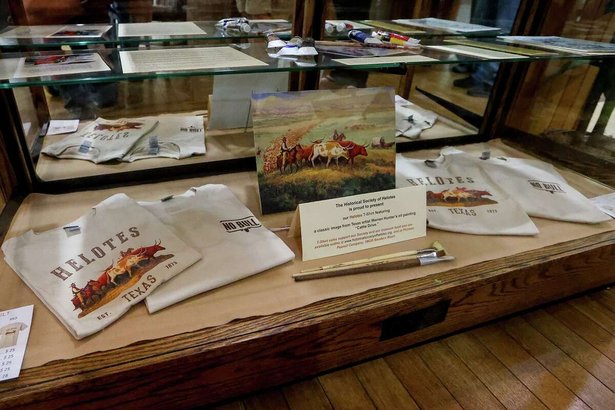 """An image of the late artist Warren Hunter's work titled """"Cattle Drive"""" and accompanying T-shirts that are for sale are shown as part of an exhibit at Helotes City Hall recently. Hunter, who resided in Grey Forest for many years prior to his death, was a prolific artist whose paintings expressed the beauty and charm of the Texas Hill Country. His work will be discussed at the Historical Society of Helotes' general meeting, from noon to 2 p.m. on Tuesday, Feb. 2, at the Gardens at Old Town, 15060 Antonio Drive. Dr. Lauren Langford, Hunter's niece, will oversee the presentation. RSVP at info@historicalsocietyofhelotes.org by Sunday, Jan. 31."""