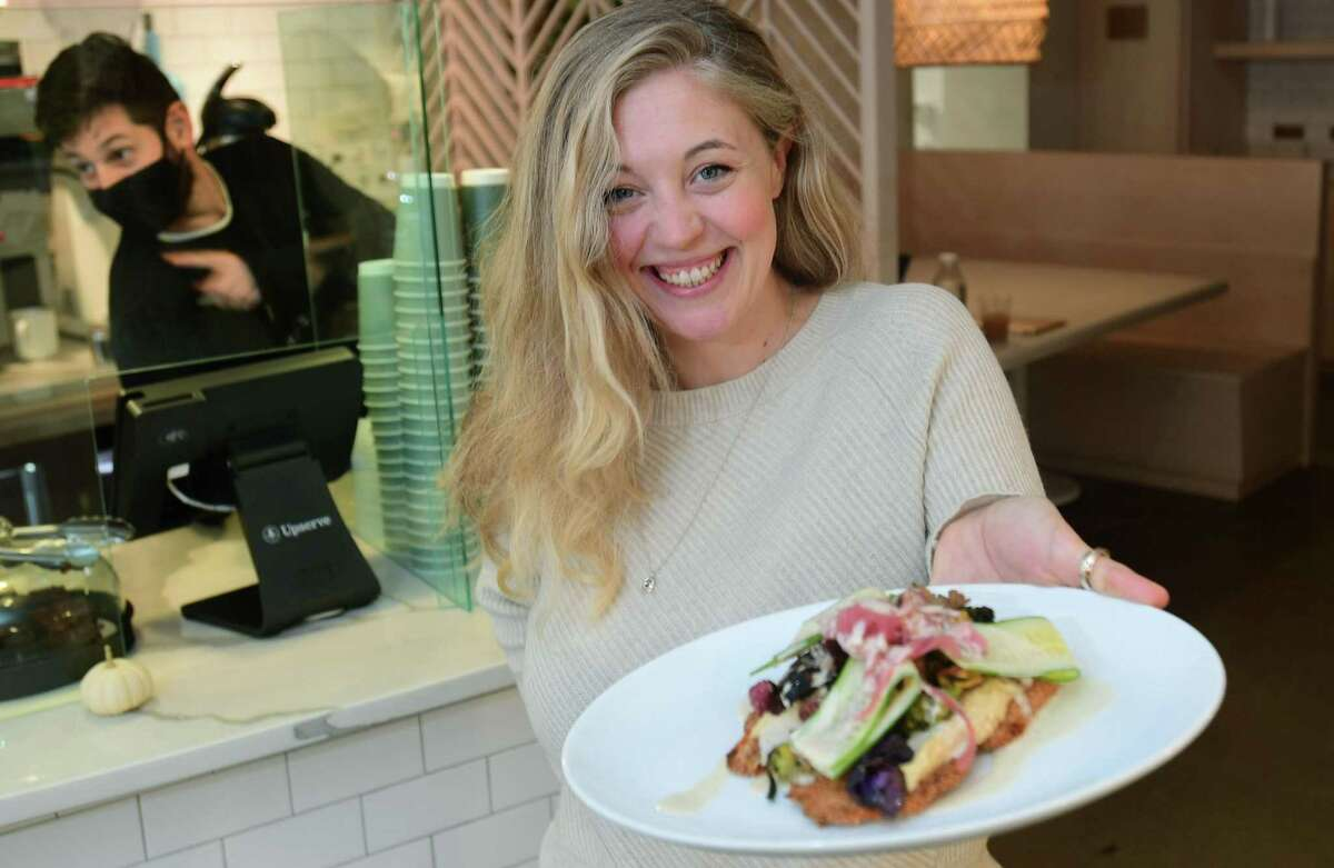 """Molly Healy, owner of Manna Toast, an artisan toast cafe, with Hummus on Sourdough, Friday, October 23, 2020, in Westport, Conn. The eatery opened during the pandemic with great success. """"Plant-based cooking is how I cook,"""" she says. """"I like to keep things healthy. I don't like manipulate food too much."""" Healey also wanted the restaurant to be somewhat casual - high-end food in a relaxed environment. The more Healey thought about it, the more toast seemed like a good vehicle for fresh, healthy toppings. Healey says open-faced sandwich shops are popular elsewhere in the world, particularly in Scandinavian countries, but aren't a widespread phenomennon in the United States. """"I think people are getting sick of deli culture - the regular old sandwich with all the cold cuts on it,"""" Healey says. """"Everybody has a taco shop, or a sandwich shop or a salad bar. We're trying to do something different."""" Most of the restaurant's sandwiches take sourdough bread sourced from Wave Hill Breads in Norwalk as their base. Most of the other ingredients are procured from area farms."""