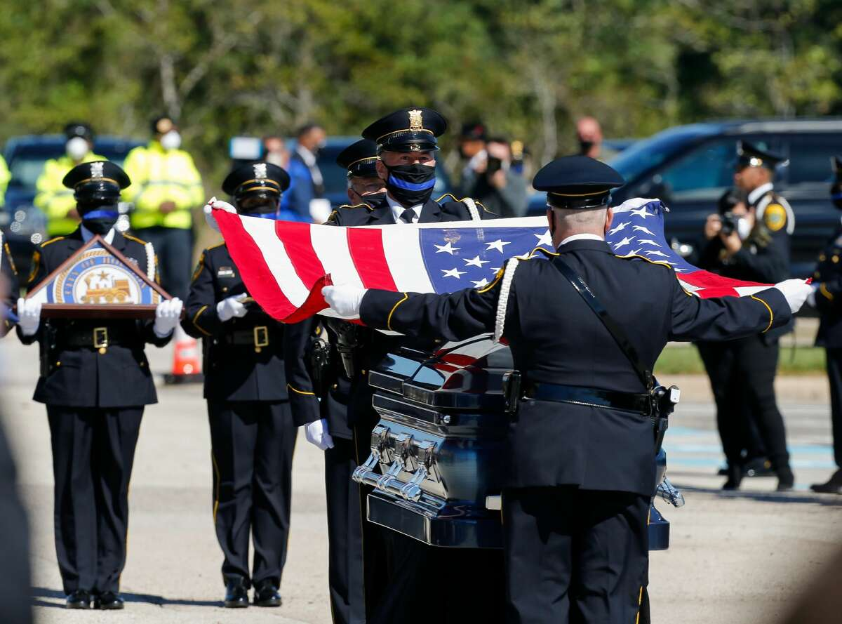 Members of the Houston Police Honor Guard fold the U.S. flag that covered the casket containing the body of Houston Police Sgt. Harold Preston during the special police honors outisde Grace Church Houston on Thursday, Oct. 29, 2020, in Houston.