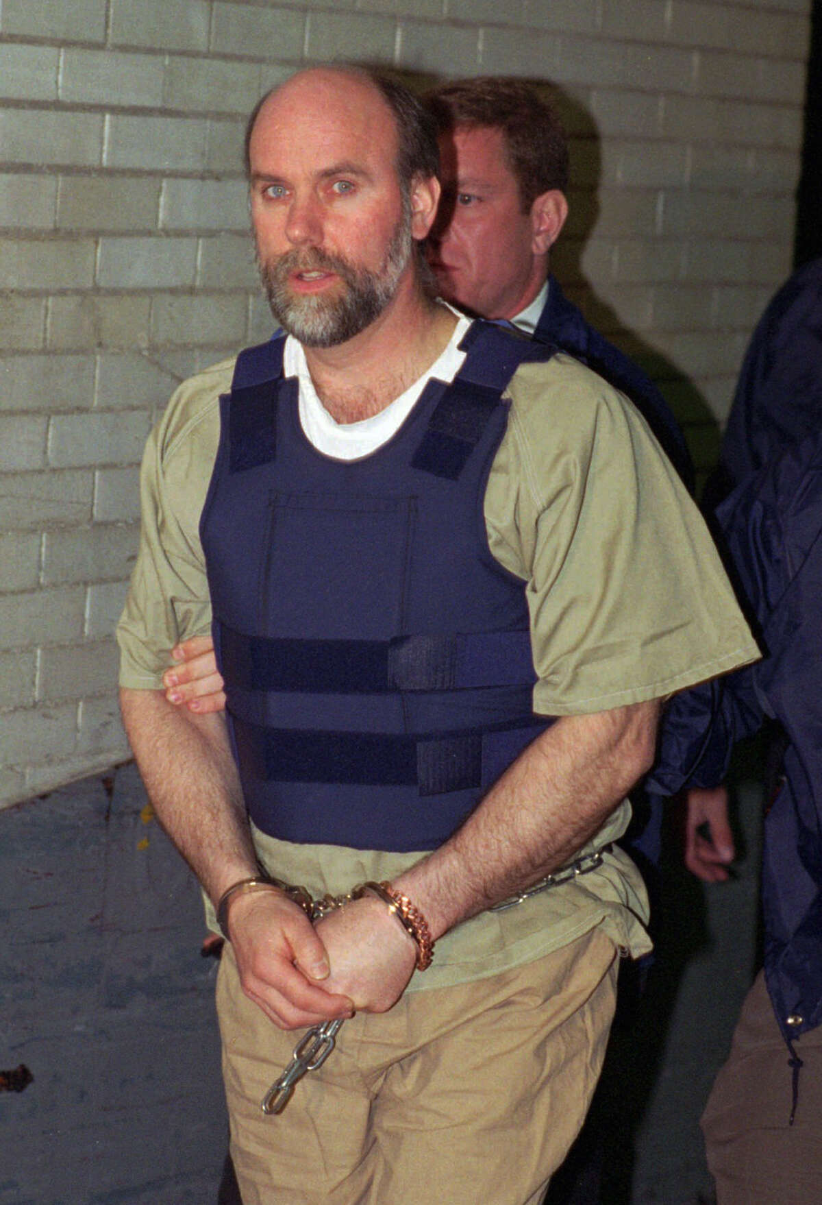 FILE - In this May 22, l995, file photo, James Nichols is escorted into the U.S. District Court building in Detroit. Nichols, the brother of Oklahoma City bombing conspirator Terry Nichols, died Tuesday, Feb. 14, 2017, in a Saginaw, Mich., hospital following a lengthy illness. He was 62. (AP Photo/Richard Sheinwald, File)