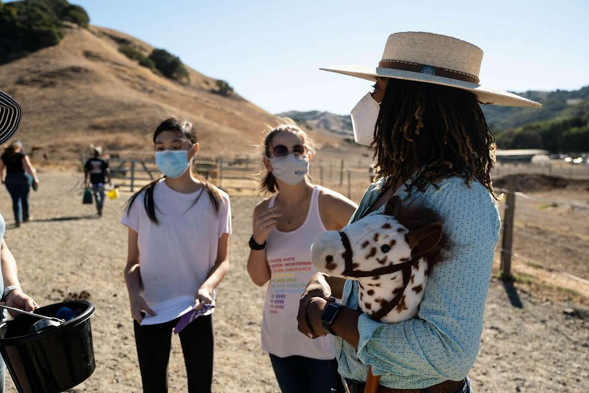 Activist, Brianna Noble, (far right) speaks with visitors at Hossmoor Ranch in Briones, Calif. on Saturday, October 17th, 2020. Brianna is committed to using her non-profit for the purpose of educating and exposing youth, who may not ordinarily get an opportunity to work a ranch or ride and care for horses. Brianna knows personally the many life lessons and areas of personal development that come from caring for horses and working a ranch.