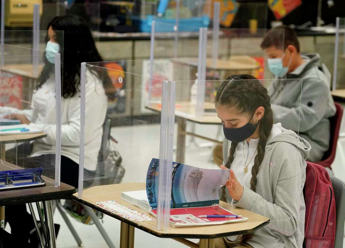 Students work behind partitions on their desk during a class at Holub Middle School Monday, Oct. 26, 2020 in Houston.