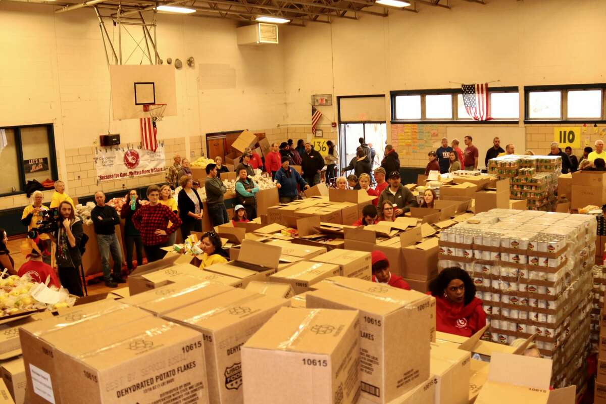 Sorting food and packing boxes at Keane Elementary School takes 320 volunteers each year before between 2,200 and 2,300 families pick up their boxes on the Sunday before Thanksgiving.
