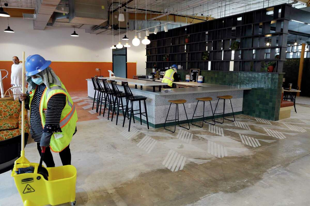 Contractors continue work around the hospitality/espresso bar in a large open common area at Common Desk, a coworking location, on Wednesday, Oct. 28, 2020 in Houston, TX. The facility is the first location in Houston by the Dallas based company and is scheduled to open Nov. 2nd.
