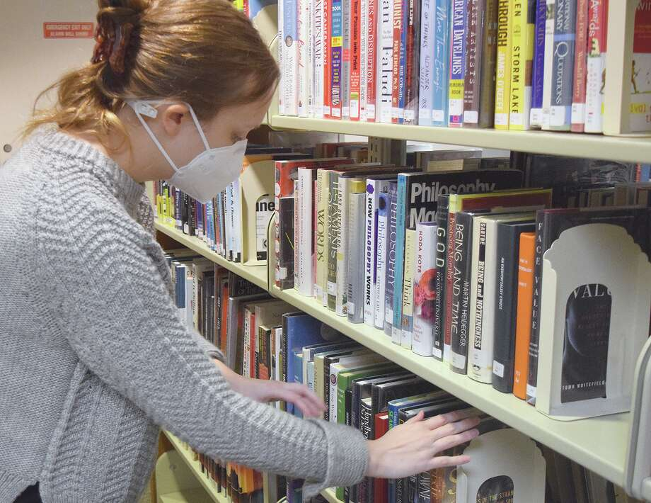 Sarah Snyder, assistant director of Jacksonville Public Library, wears a mask as she arranges books at the library. She is in support of wearing masks in public settings. Photo: Rochelle Eilselt | Journal-Courier