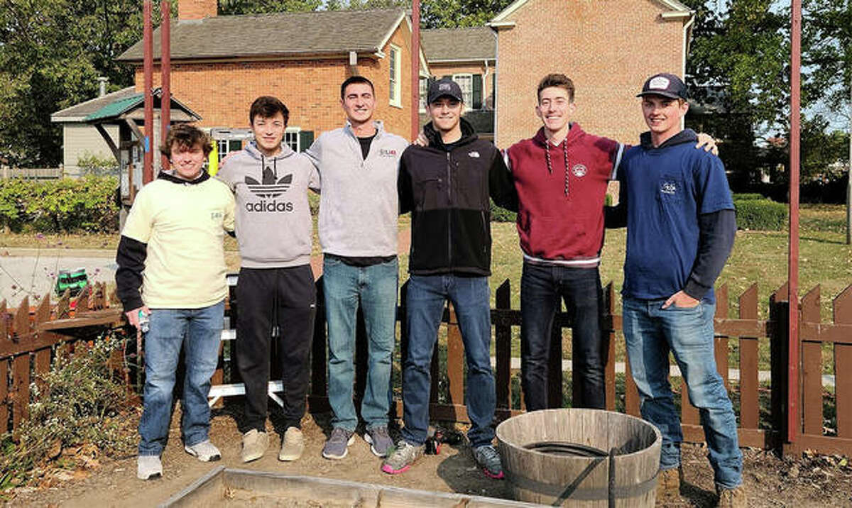 Members of Southern Illinois University Edwardsville's Sigma Phi Epsilon fraternity work on beautifying the gardens at 1820 Col. Benjamin Stephenson House Saturday. Members of Southern Illinois University Edwardsville's Sigma Phi Epsilon fraternity pose in the garden.