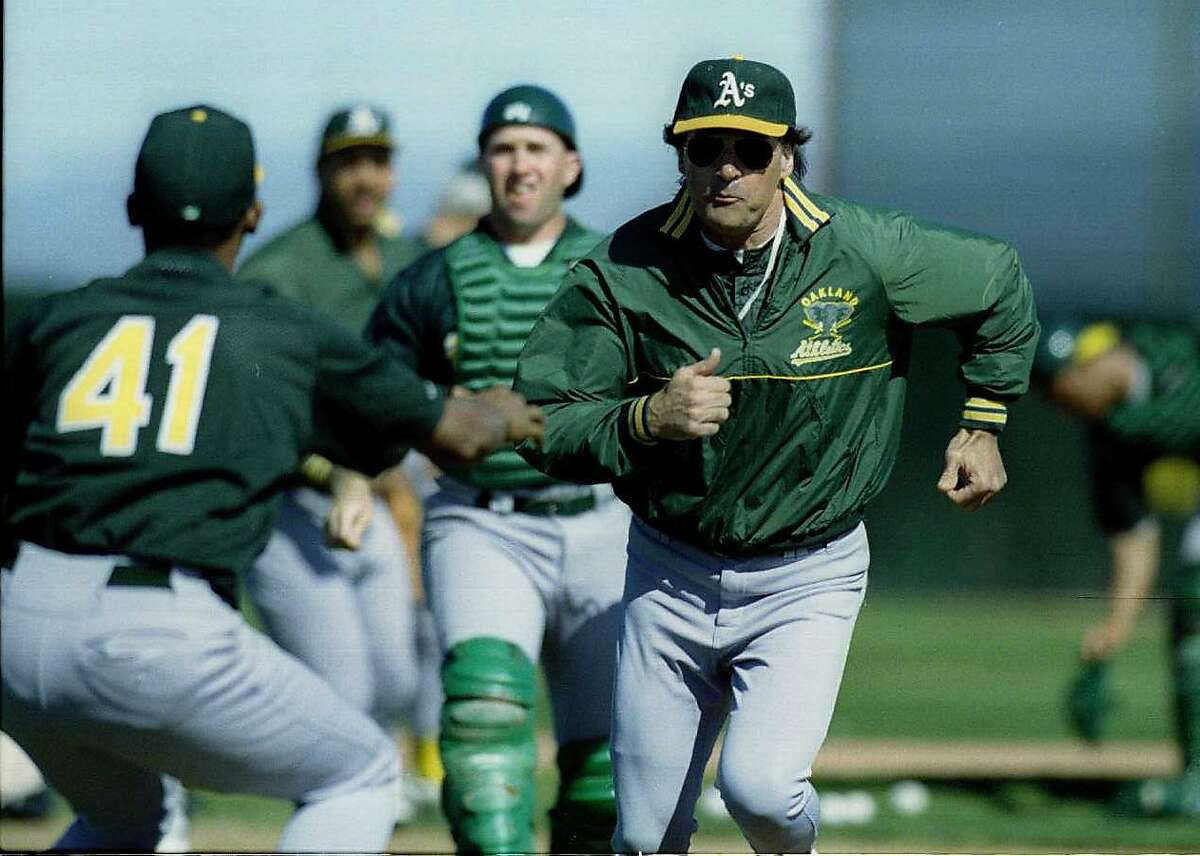 Baseball Spring Training: Oakland A's manager Tony La Russa tries to avoid the tag of Fausto Cruz during team run down drills.