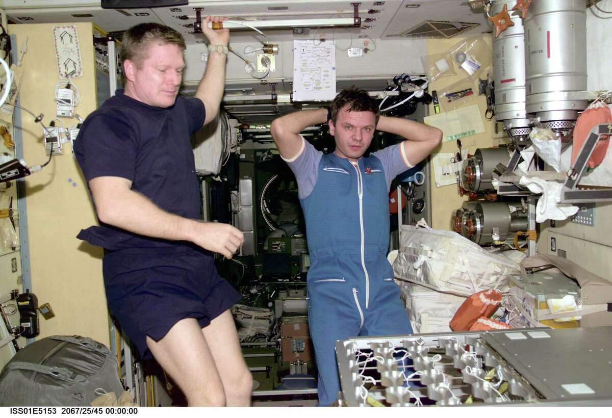 Astronaut William M. Shepherd and cosmonaut Yuri P. Gidzenko contemplate work they're doing on the food warmer for the Ward Room table aboard the International Space Station's Zvezda Service Module.