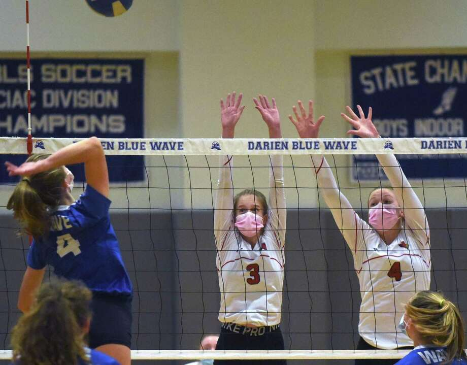 Greenwich's Addie Leder (3) and Cornelia Roach (4) go up to try and block a shot from Darien's Ellie Moore (4) during a girls volleyball match in Darien on Thursday. Photo: David Stewart / Hearst Connecticut Media / Connecticut Post