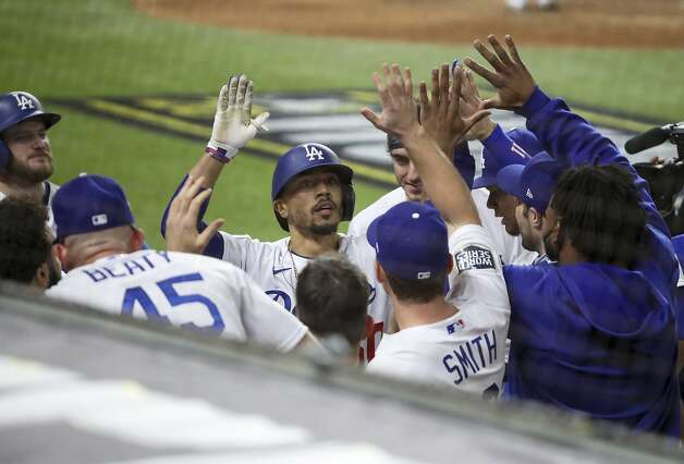 The Los Angeles Dodgers' Mookie Betts, middle, is congratulated after hitting a solo home run in the eighth inning against the Tampa Bay Rays in Game 6 of the World Series at Globe Life Field in Arlington, Texas, on Tuesday, Oct. 27, 2020. The Dodgers won, 3-1, to clinch the series. (Dirk Shadd/Tampa Bay Times/TNS) Photo: Dirk Shadd, TNS