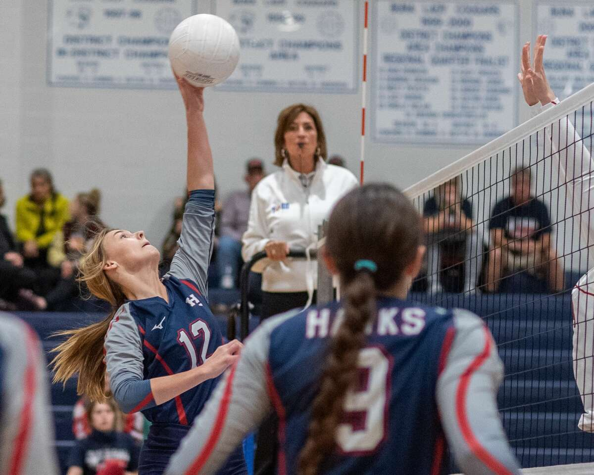 The Lady Hawk's Lauren O'Neal (12) slams a shot in the middle of traffic. The Lady Cardinals of Bridge City took down the Lady Hawks of Hardin-Jefferson in 4 sets on Thursday night in the bi-district volleyball match at Buna High School. Photo made on October 29, 2020. Fran Ruchalski/The Enterprise