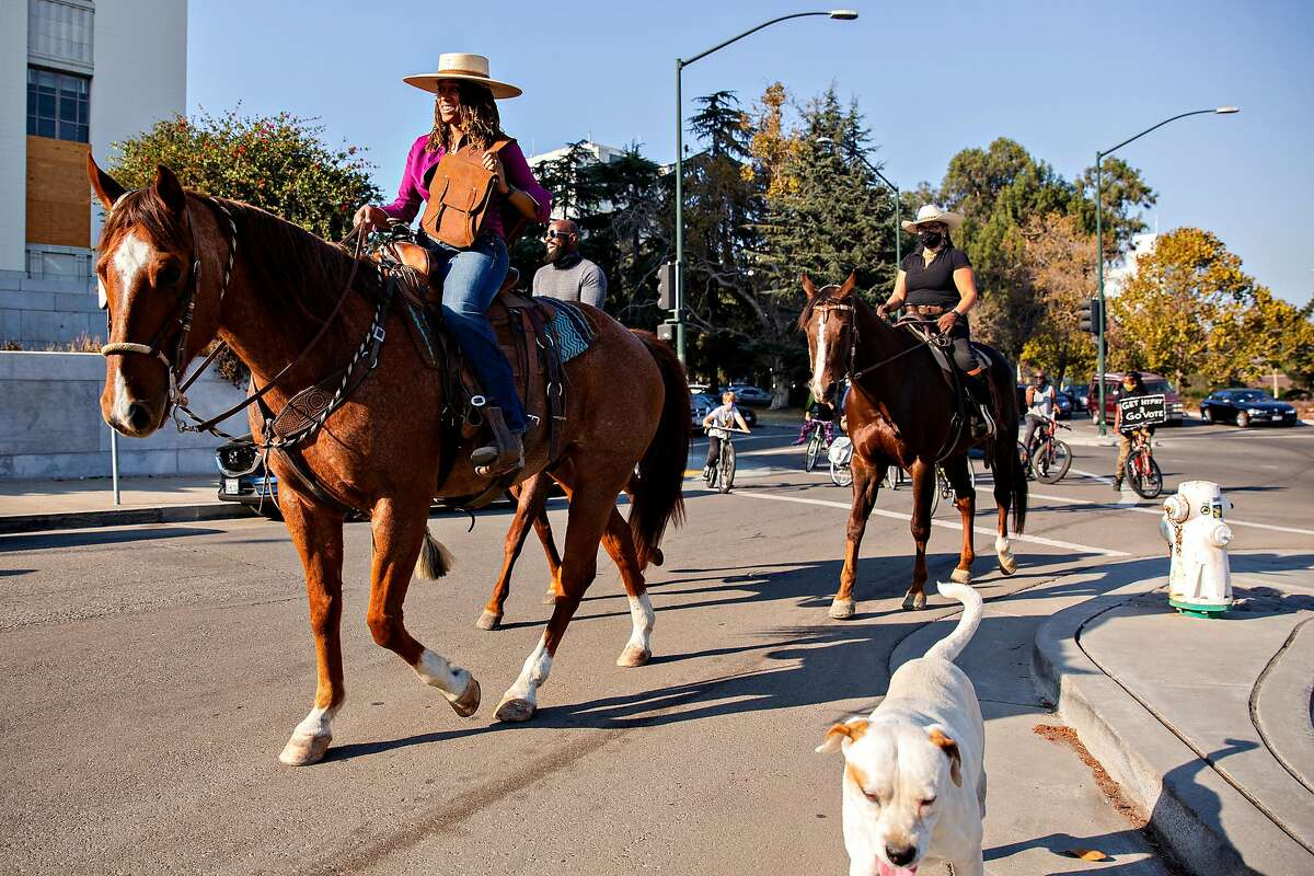 Brianna Noble (center) rides her horse Dapper Dan down Fallon street with fellow riders Dale Johnson and Rachel Royce along with several bicyclists in Oakland, Calif. on Thursday, Oct. 29, 2020. Noble led the get out the vote event #rideouttovote from Laney College to the Alameda County Courthouse to drop off her ballot along with other riders.