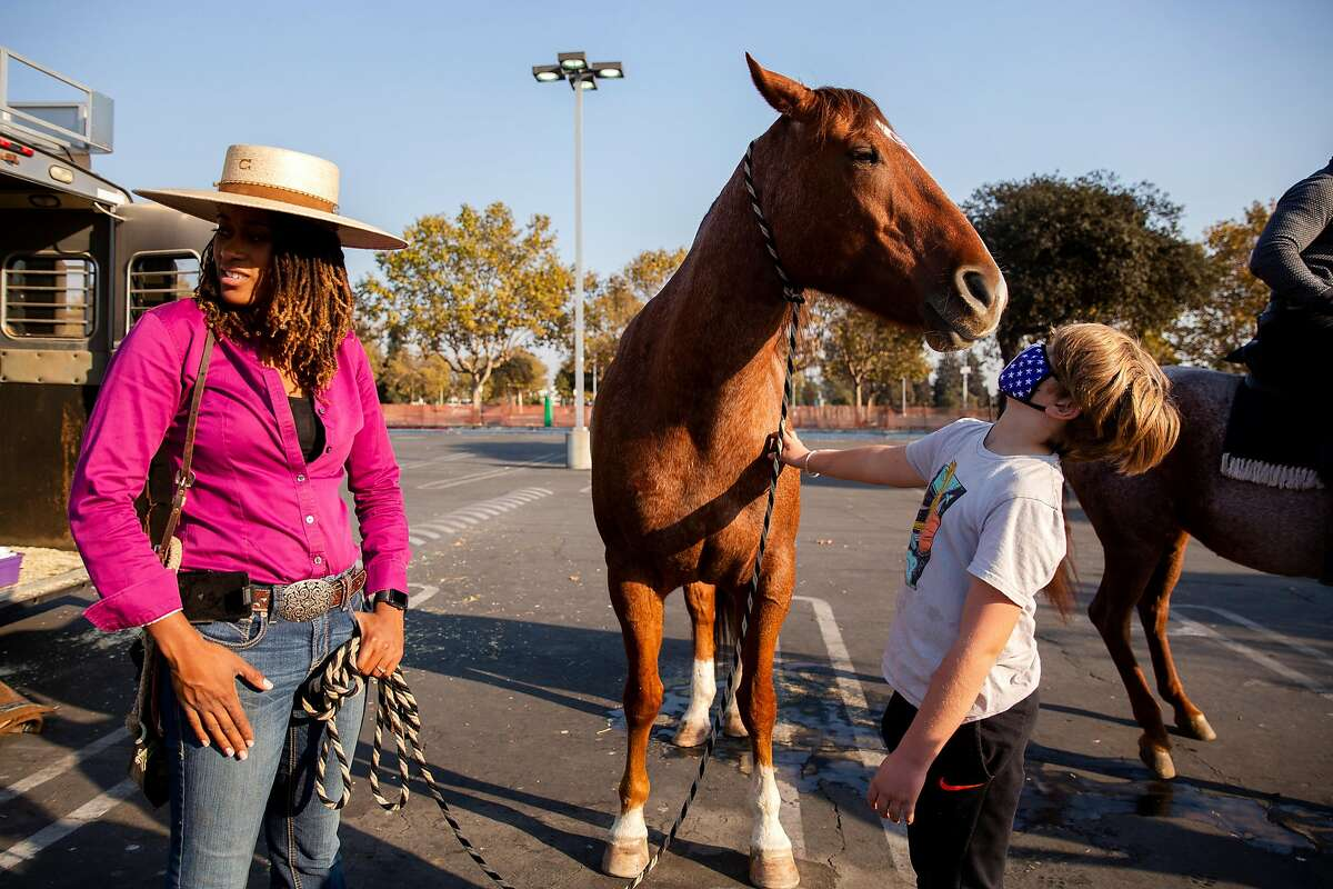 Uli Spoerl, 10, pets Brianna Noble's horse Dapper Dan in Oakland, Calif. on Thursday, Oct. 29, 2020. Noble led the get out the vote event #rideouttovote from Laney College to the Alameda County Courthouse to drop off her ballot along with other riders.