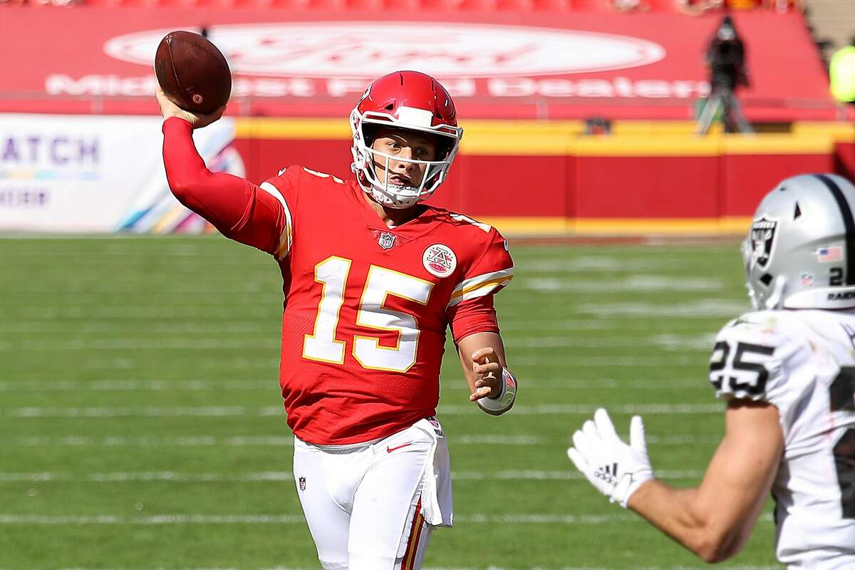 Kansas City Chiefs quarterback Patrick Mahomes (15) throws a touchdown pass under pressure from the Las Vegas Raiders' Erik Harris (25) on October 11 at Arrowhead Stadium in Kansas City, Missouri.