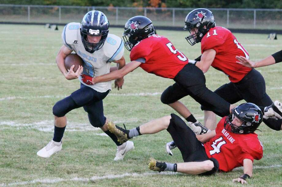 Brethren's Jake Schuch looks for room to run while being pursued by Bear Lake defenders during the teams' regular season meeting on Sept. 25. The Bobcats and Lakers will collide again at 7 p.m. on Saturday at Bobcat Field for a 8-Player Division 2 playoff opener. (News Advocate file photo)