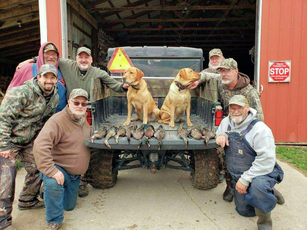 Local hunters pose with labs Rambo and Madie, a father and daughter team. The hunters are, at left, Ted Platz, Tyler Thompson, Mark Curtiss and Lyle Lodholtz; at right, Terry Getts, Howie Lodholtz and Al Remus. (Courtesy photo)