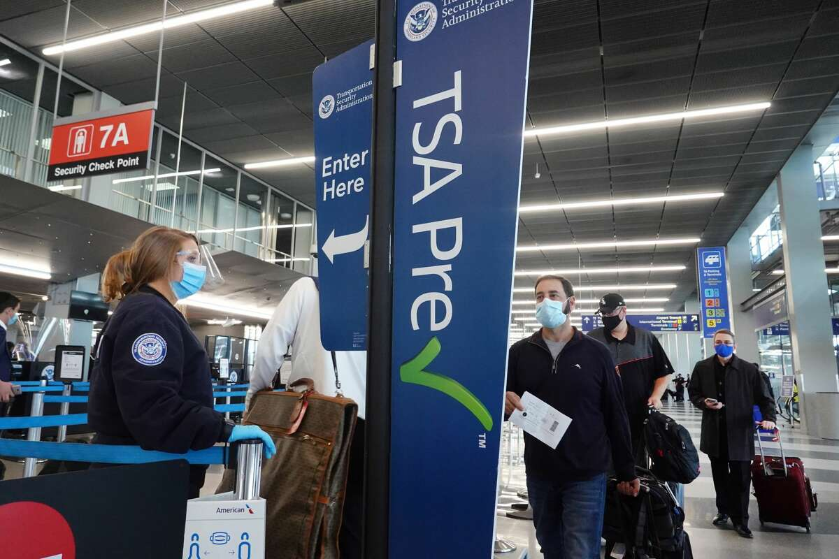 Passengers wait in a TSA pre-check line before boarding their flights.