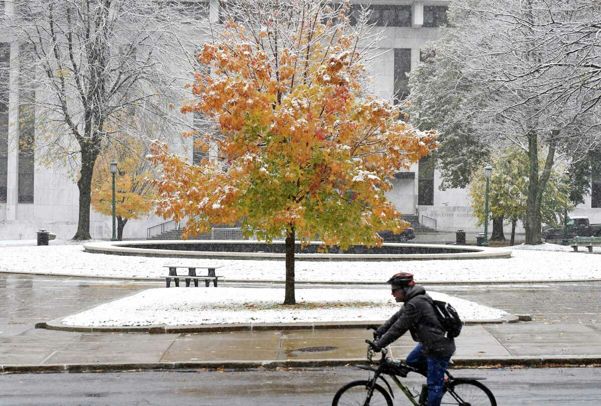 A cyclist rides down Washington Avenue past the Capitol as the first snowfall of the season arrives in the Capital Region on Friday morning, Oct. 30, 2020, in Albany, N.Y. (Will Waldron/Times Union)