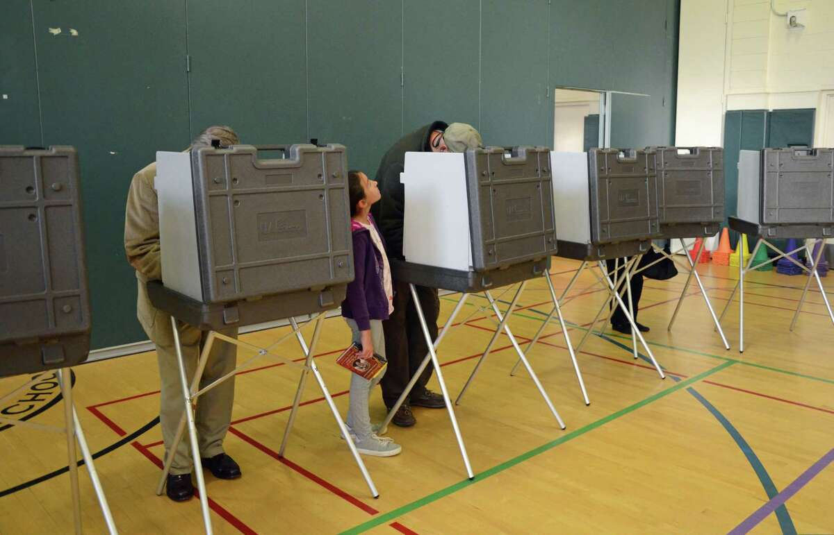 A young girl stands next to a voter during a recent day of voting in Greenwich.