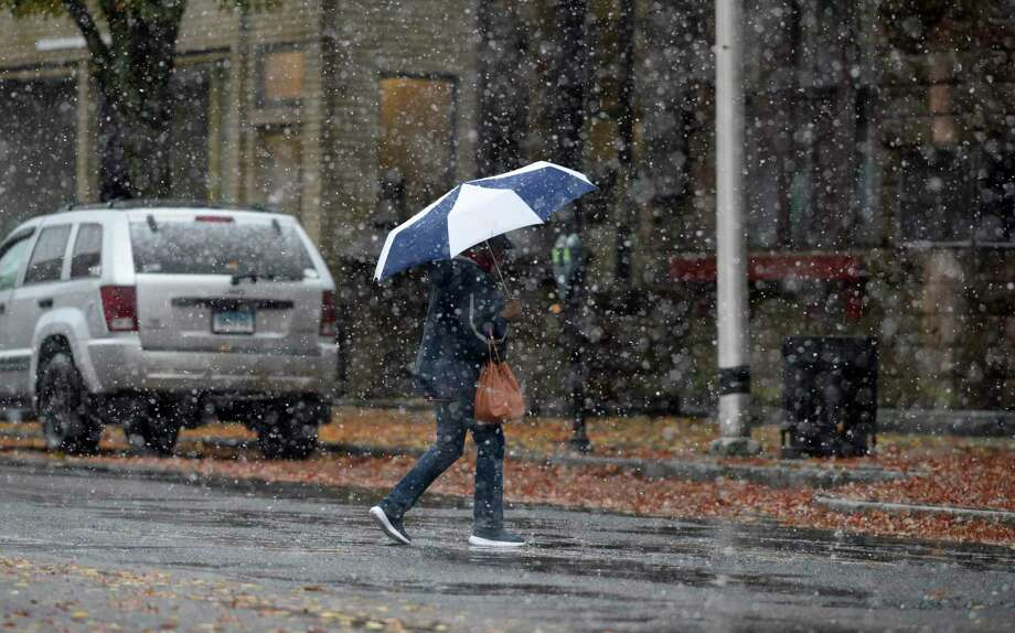 A pedestrian uses an umbrella to protect themselves from the wet snow that fell across the Danbury area on Friday morning as they cross Main Street. October 30, 2020, Conn. Photo: H John Voorhees III / Hearst Connecticut Media / The News-Times