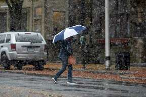 A pedestrian uses an umbrella to protect themselves from the wet snow that fell across the Danbury area on Friday morning as they cross Main Street. October 30, 2020, Conn.