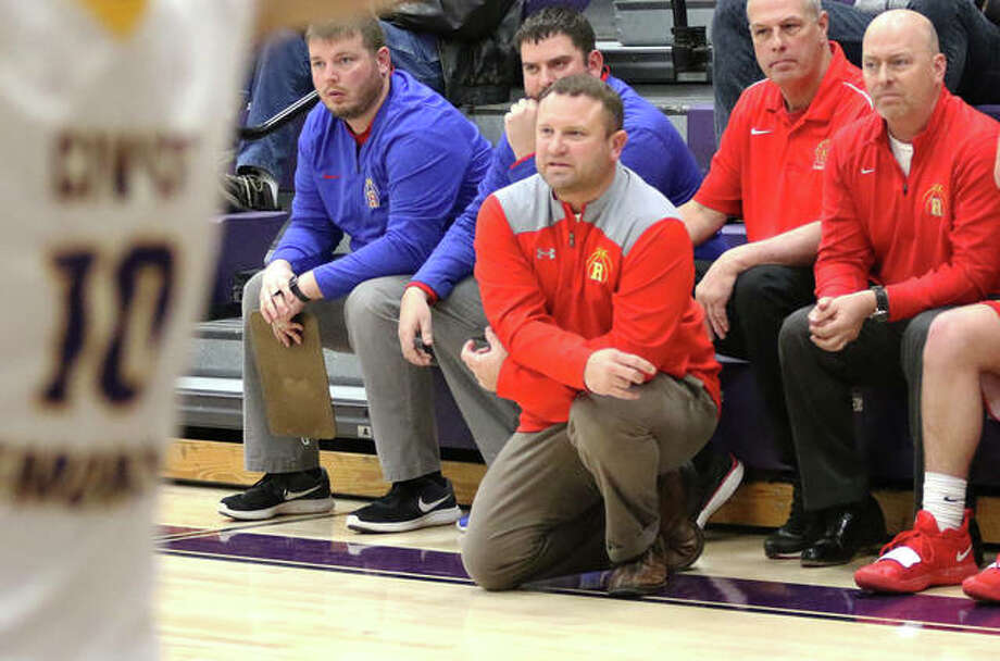 Roxana coach Mark Briggs (kneeling) watches his team play last season. The IHSA has elected to go ahead with plans to play boys and girls basketball this winter season, despite the Illinois Department of Public Health placing the sport in the high risk category. Briggs is also the Roxana High athletic director. Photo: Telegraph File Photo