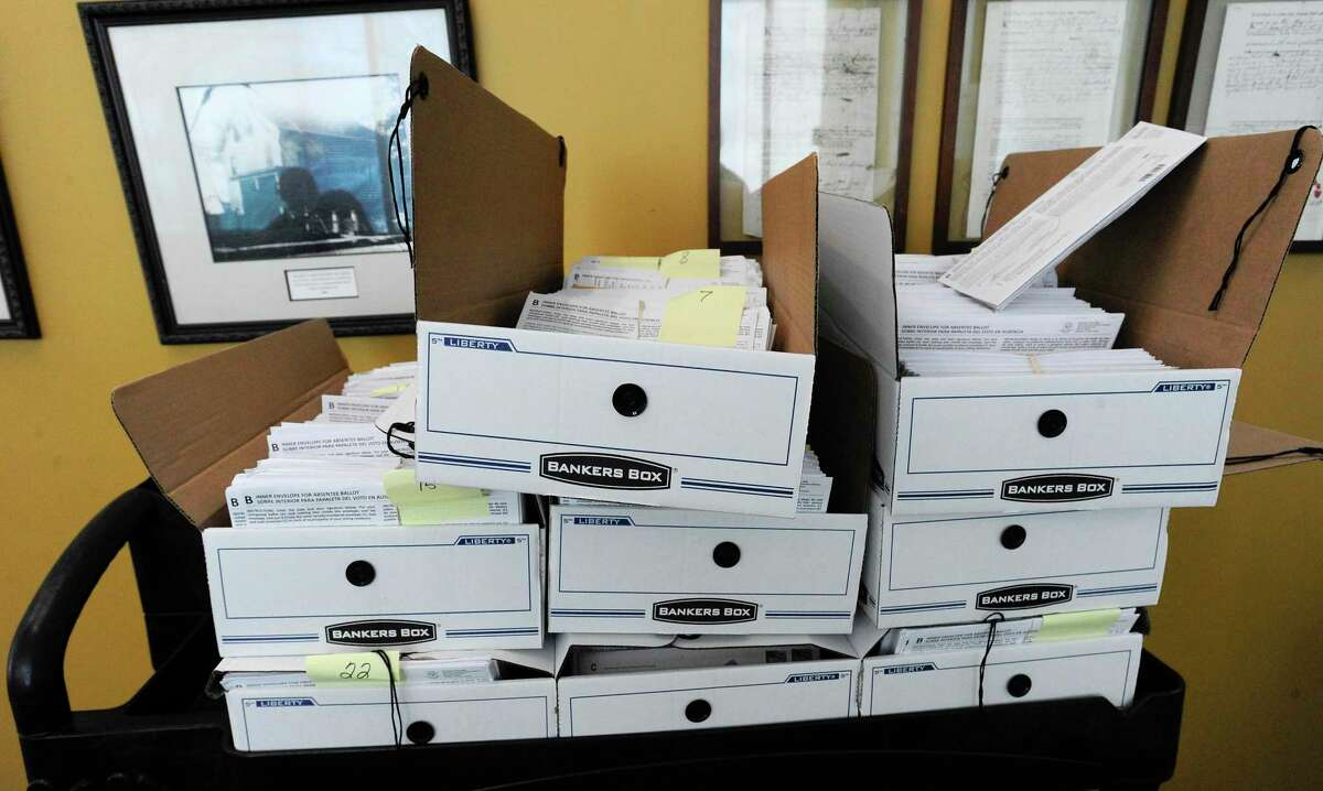 Stack of trays of absentee ballots await counting in advance of Election Day on Tuesday.
