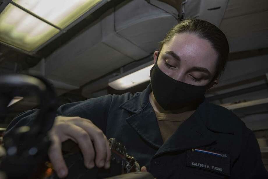 Aviation Electronics Technician Airman Kaleigh Fuchs of New Haven performs maintenance on an infrared targeting system in the aviation electrical optics shop of the Navy's only forward-deployed aircraft carrier USS Ronald Reagan (CVN 76). Ronald Reagan, the flagship of Carrier Strike Group 5, provides a combat-ready force that protects and defends the United States, as well as the collective maritime interests of its allies and partners in the Indo-Pacific region. Photo: Mass Communication Specialist 3rd Class Quinton A. Lee / Contributed Photo
