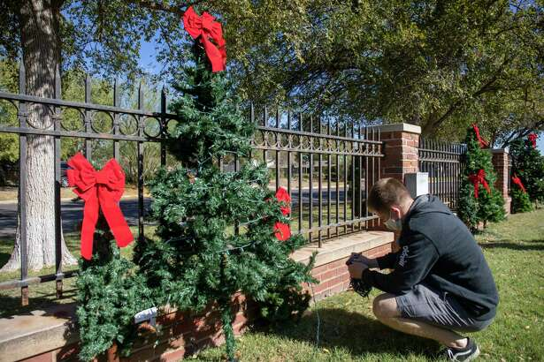 Elder Compas, a volunteer from the Church of Jesus Christ of Latter-day Saints, puts final touches on a tree display for a different type of Christmas at the Mansion this year on Thursday, Oct. 29, 2020 at the Museum of the Southwest. Jacy Lewis/Reporter-Telegram