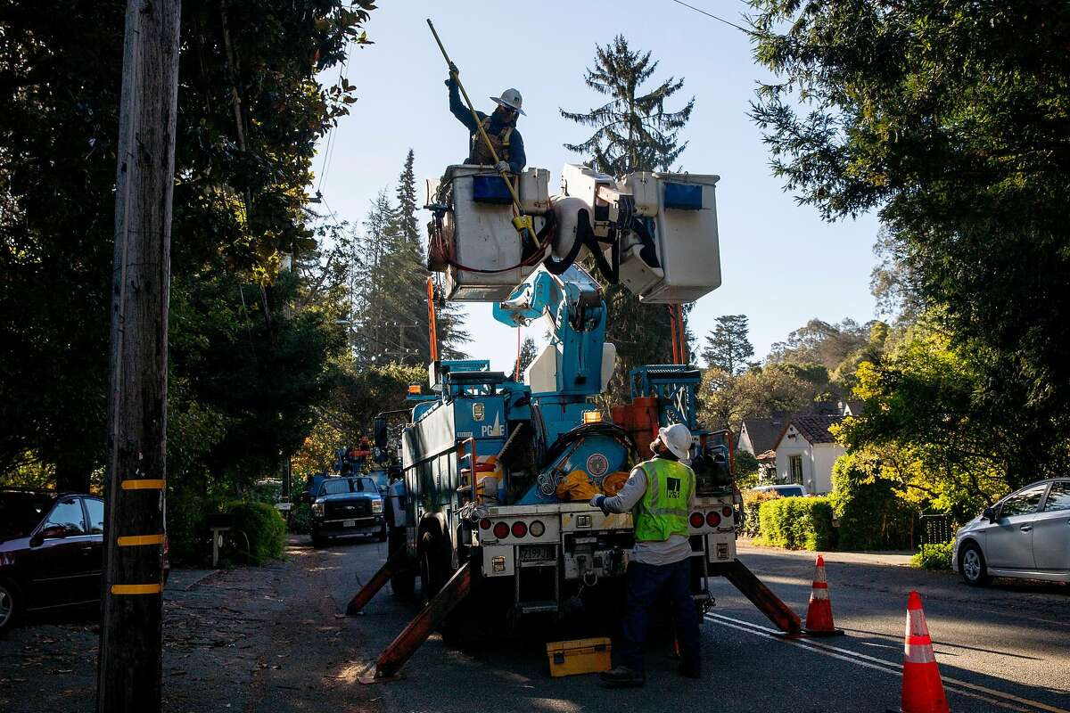 PG&E line inspector Kirk Thompson works to clear lines so crews can begin removing a tree that crashed into live power lines along Mountain Boulevard in the Montclair Village neighborhood of Oakland on Oct. 15.