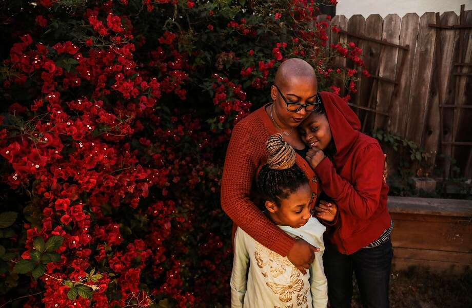 Brandii Hudson of East Oakland hugs niece Zaylynn Hunter (right), 10, and daughter Nyla Hudson, 9. Photo: Yalonda M. James / The Chronicle