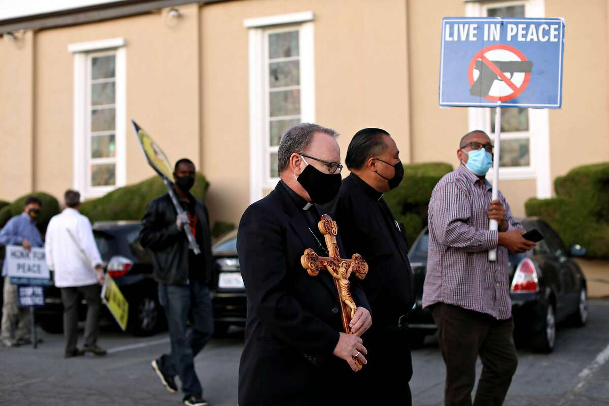 Oakland Bishop Michael Barber carries a cross alongside the Rev. Jayson Landeza of St. Benedict Catholic Church in Oakland during a Ceasefire Night Walk in Oakland in October.