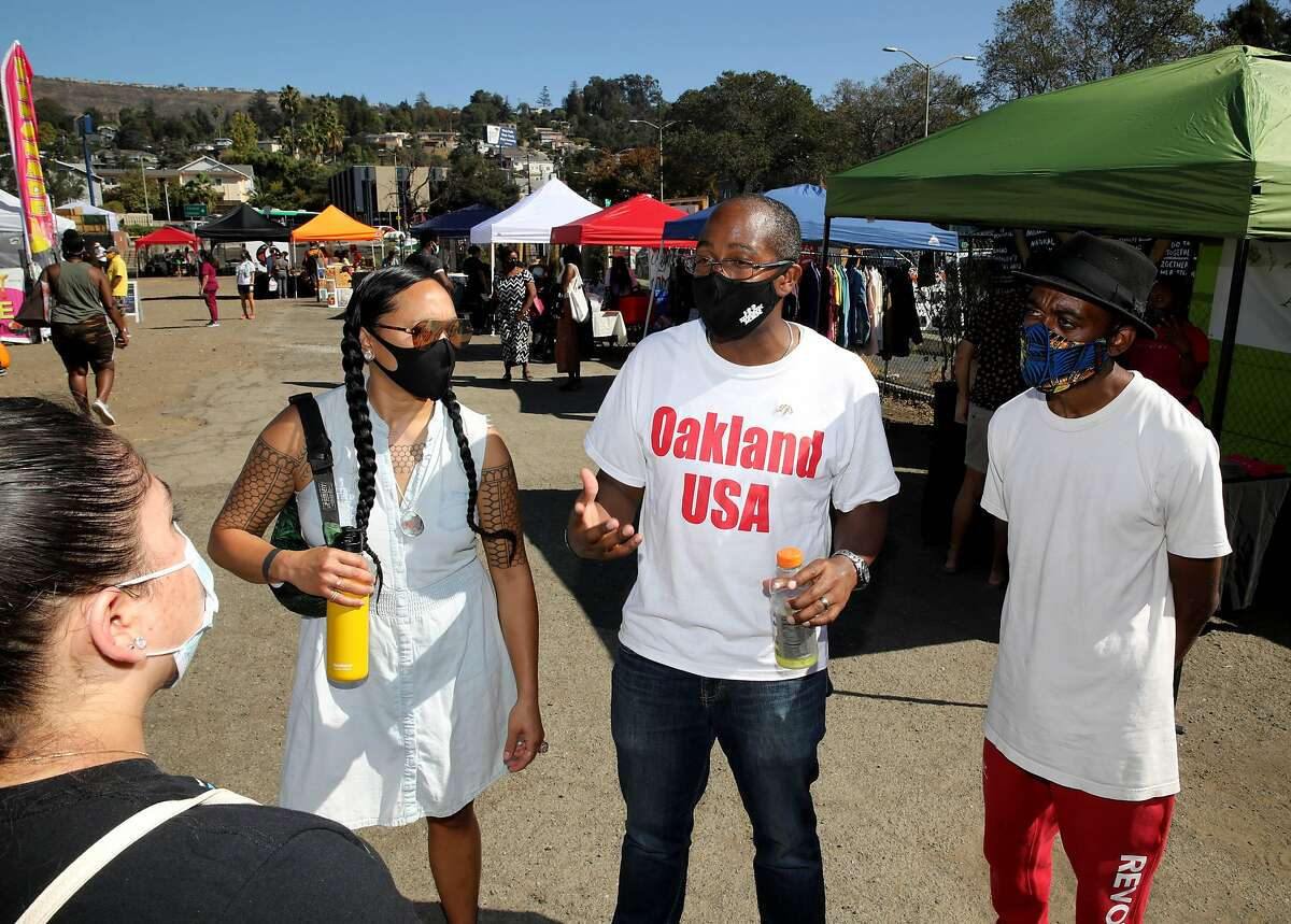 Oakland councilman Loren Taylor (District 6), center, is flanked by Eden Silva Jequinto, left, and Sizwe Andrews - Abakah, right, and others as he meets with Oakland residents at the Akoma Outdoor Market on Sunday, October 18, 2020, in Oakland, Calif. Taylor is co-chairing the Reimagine Public Safety Taskforce. At the height of the summer's racial justice protests, Oakland city leaders, like so many of their counterparts across the country, floated an audacious proposal to reshape public safety: cut the police budget in half, and shift many of its responsibilities over to civilians. To accomplish the goal, the City Council put together a task force with members from all sides of Oakland's varied cultural diaspora, from budget hawks, to activists who had protested the police for years. Now they're scrambling to deliver a plan by June and sell it to a city of skeptics and neighborhoods rattled by a violent crime wave, merchants weary of civil unrest downtown, people who agreed with the vision but thought the task force was just lip service. Other cities, including Minneapolis, had already failed to meet the promises they made the summer, and nationally, support for Black Lives Matter appears to be flagging. Oakland, with 17 years under federal watch, a recent sexual misconduct scandal and a long history of cycling through chief after chief, seemed like an unlikely torchbearer. But despite the odds, city politicians are convinced they can pull it off.