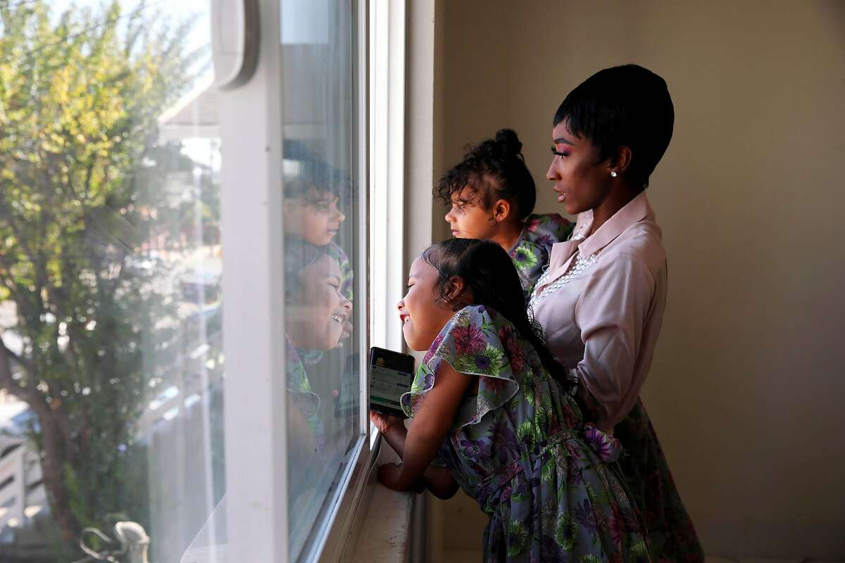 Keisha Henderson and her twin daughters, Bethany Hicks (left) and Brittany Hicks look outside from their East Oakland home in October. Henderson hasn't let her children walk their block because of a fear of crime.