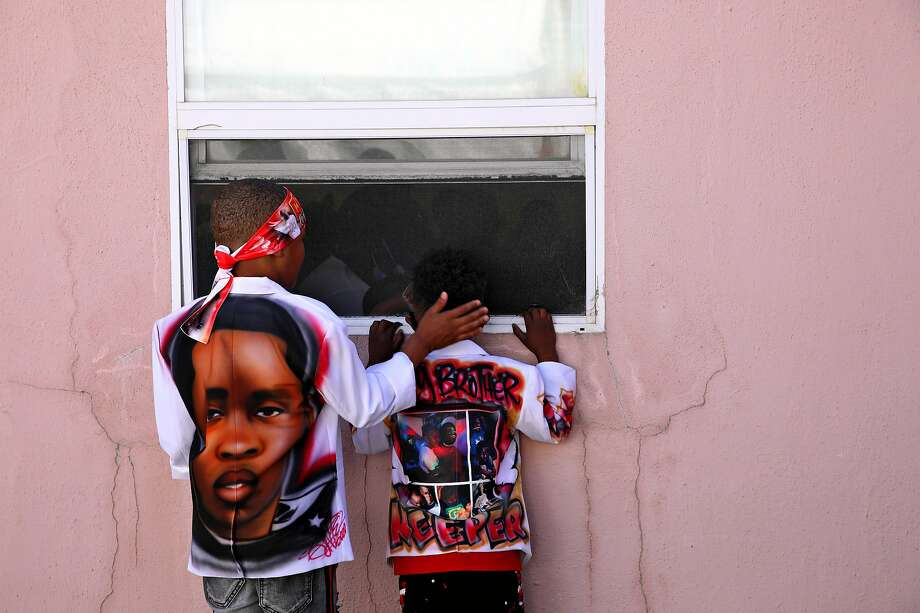 Trayvon Hall (left), 7, comforts his cousin, Kai Pryor, 4, as he peeks through a window during the funeral service for his older brother Aaron Pryor, a 16-year-old star athlete who was shot to death i near his home in September. Photo: Photos By Yalonda M. James / The Chronicle