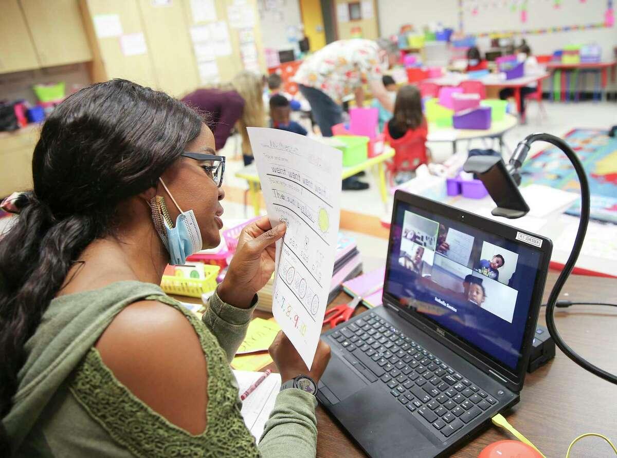 Stafford MSD kindergarten teacher Johanna Chesser teaches an online class from her classroom at Stafford Early Childhood Center while music teacher Brian Vaughn watches over her in-person class in Stafford, Texas on Tuesday, Oct. 27, 2020.