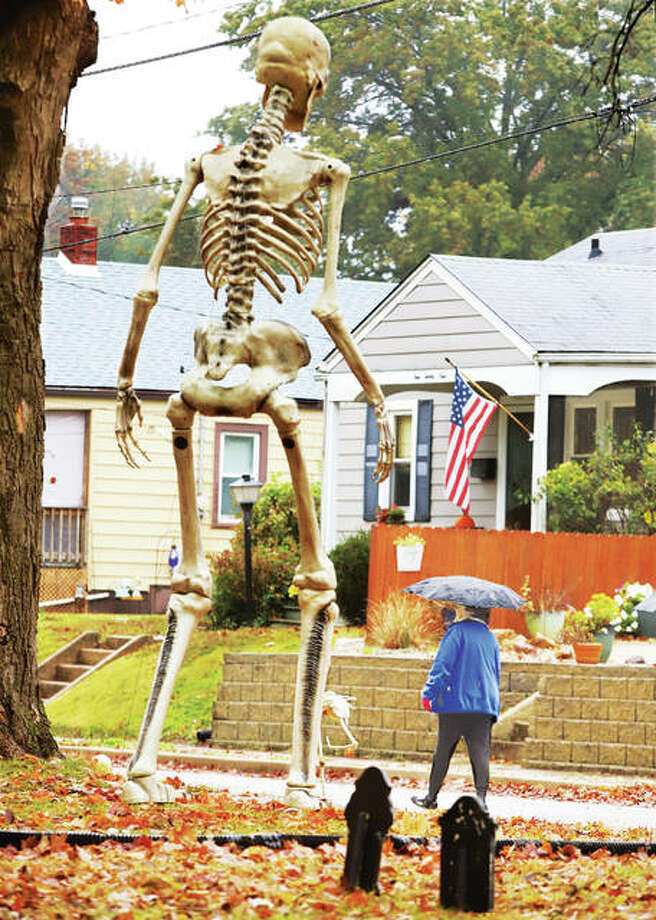 A woman goes for a walk in the rain Tuesday past the sizable skeleton Halloween decoration in the 900 block of Hawley Avenue in Alton. The towering torso is some 12 feet high and a real eye opener.