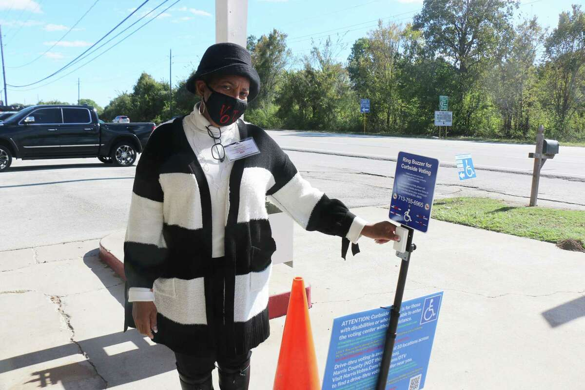 Precinct Judge Betty Vaughn shows the button on the curbside sign for patrons who would rather vote outside can push and a poll worker will come out and assist them with voting.