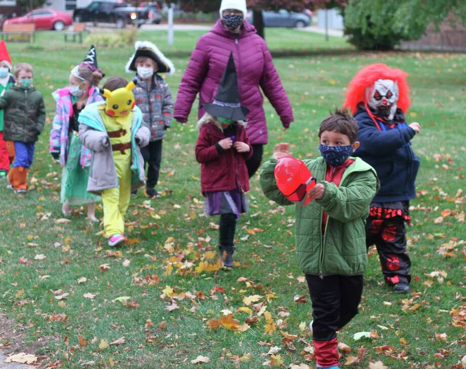Kindergarten students march along the Bryant Avenue sidewalk during Jefferson Elementary School's costume parade Friday morning. (Kyle Kotecki/News Advocate)