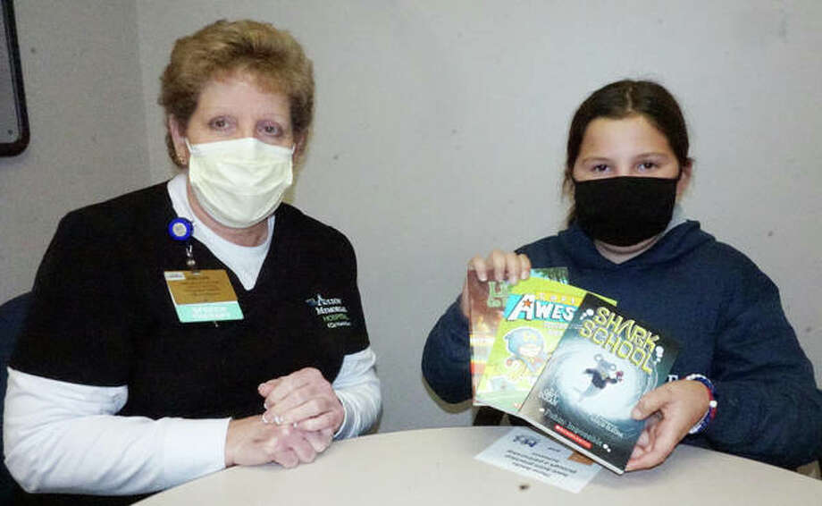 Joellen Corona, a speech therapist at Alton Memorial Hospital, helps 11-year-old Ella Curry of Alton read some of the books from the 10,000th book bag donated by Books for Newborns, which was delivered this week to AMH.