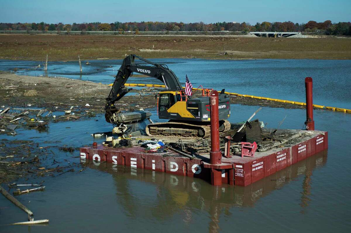 Workers with Fisher Contracting continue removing pieces of debris from the Sanford Dam Wednesday, Oct. 28, 2020 in downtown Sanford. (Katy Kildee/kkildee@mdn.net)