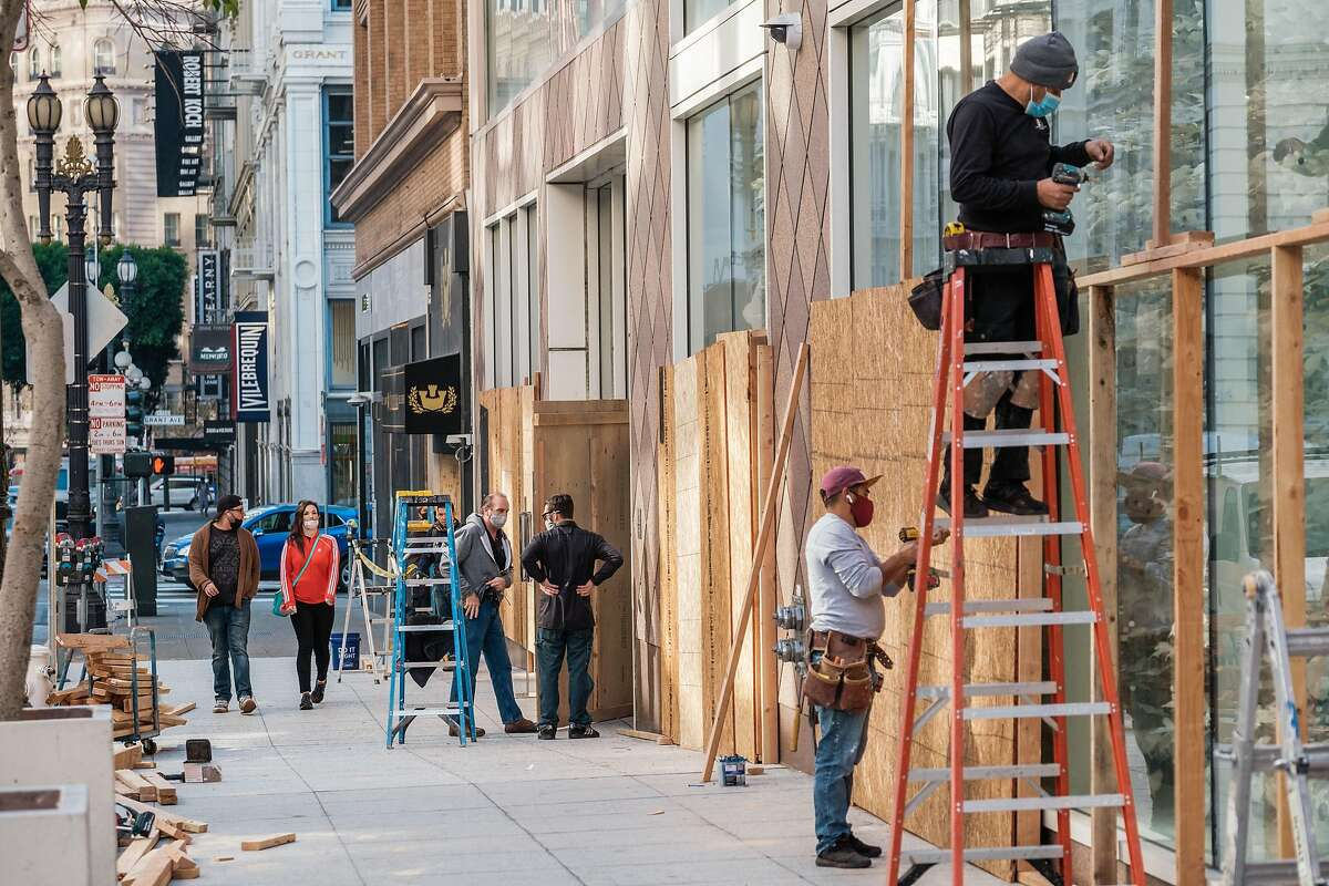 Pedestrians walk past a construction crew as they board up shop windows near Union Square in San Francisco. Cities and business are preparing for election night unrest.
