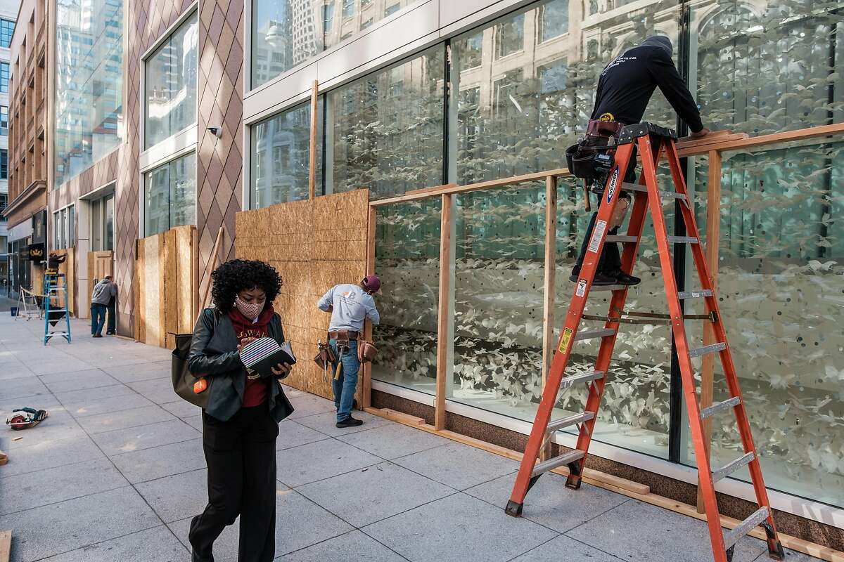 A pedestrian walks past a construction crew as they board up shop windows near Union Square in San Francisco.
