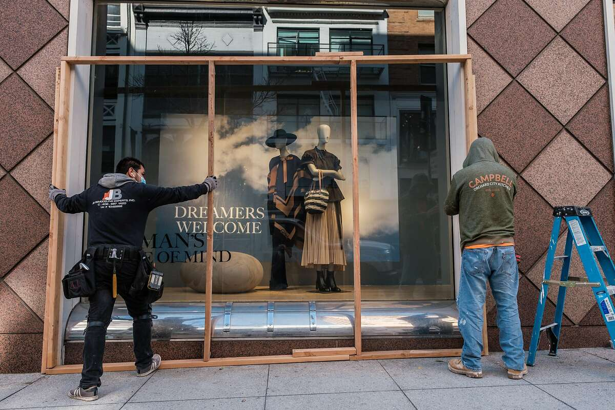 A construction crew boards up windows at Nieman Marcus near Union Square in San Francisco.