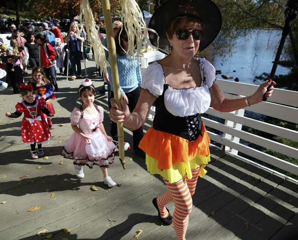 """Volunteer Joan Fischer leads the parade for children dressed up in Halloween costumes at the Stamford Museum & Nature Center in 2012. """"Halloween clearly looks very different this year,"""" said Megan Brown, youth and family programs manager at the Bruce Museum in Greenwich. """"One thing families are looking to us for is to get out, especially while it's still relatively safe, to go somewhere safe."""" Brown hopes that families can celebrate the holiday safely and festively with the museum's Tricks 'n' Treats at the Bruce, scheduled for both Halloween and the day after. The event will feature a themed scavenger hunt and take-home bags full of treats and crafts for children to do at home. But planning a socially distant event for excited children on a holiday crammed with sweets and mischief isn't easy. Festivities on both days are capped to 50 people, and families must make reservations to attend, according to Brown. The scavenger hunt was more difficult to manage, since it involves people freely bustling about, but even that has been modified for the COVID-19 era."""