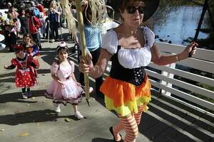 Volunteer Joan Fischer leads the parade for children dressed up in Halloween costumes at the Stamford Museum & Nature Center in 2012.