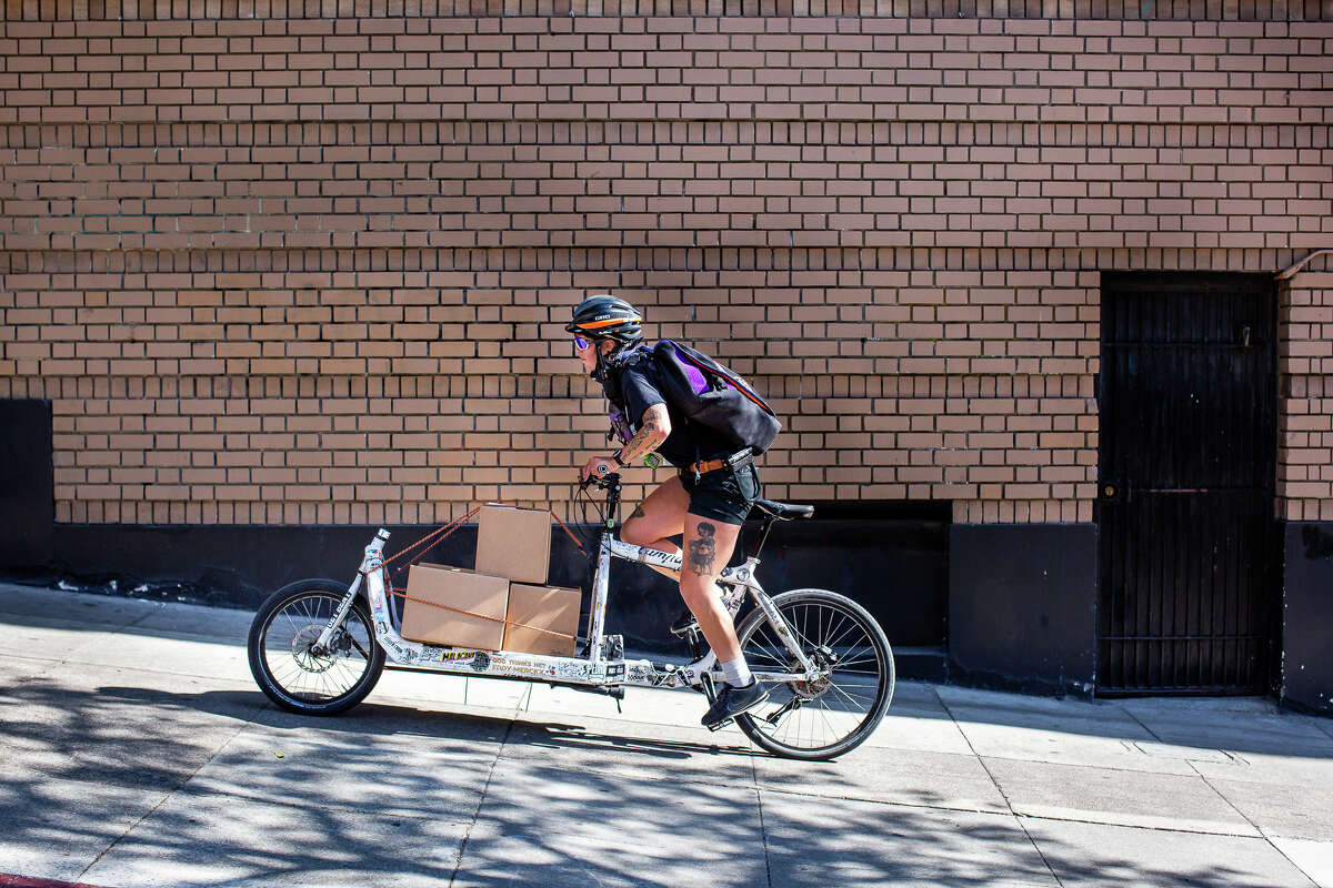 Monica Rocha, a courier at Stella Courier, rides her bike up a steep hill to deliver packages.