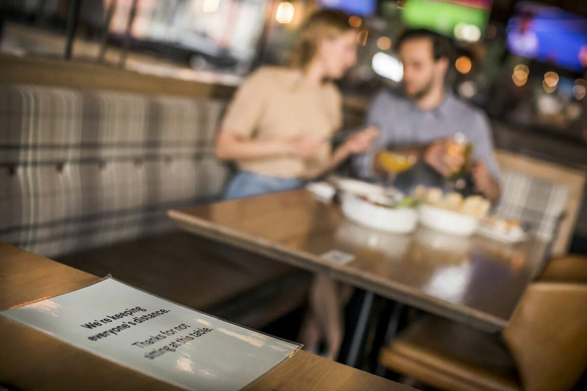 A sign reminds patrons to maintain physical distance from other diners at a restaurant.