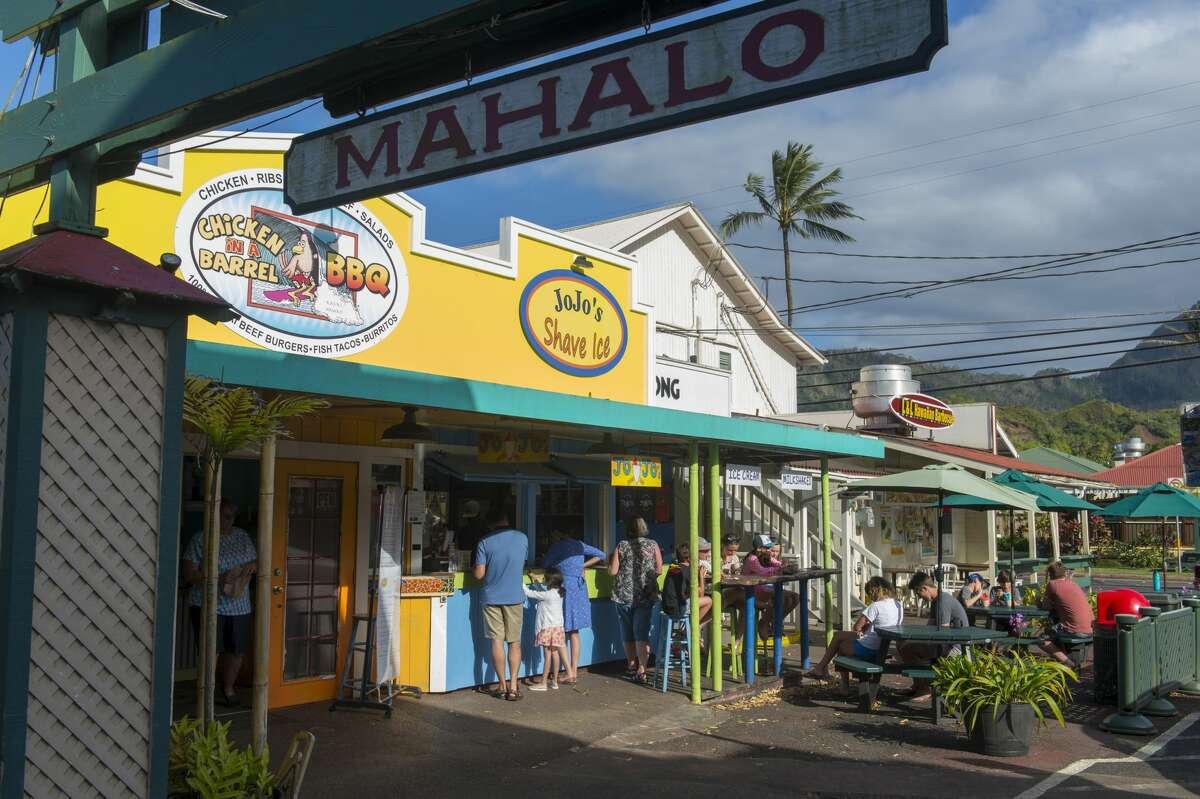 Many small businesses, like these shops and boutiques in Hanalei on the northern end of the Hawaiian island of Kauai, depend on visitors to survive. But there's a growing tension between visitors and tourists as Hawaii reopens to travelers.